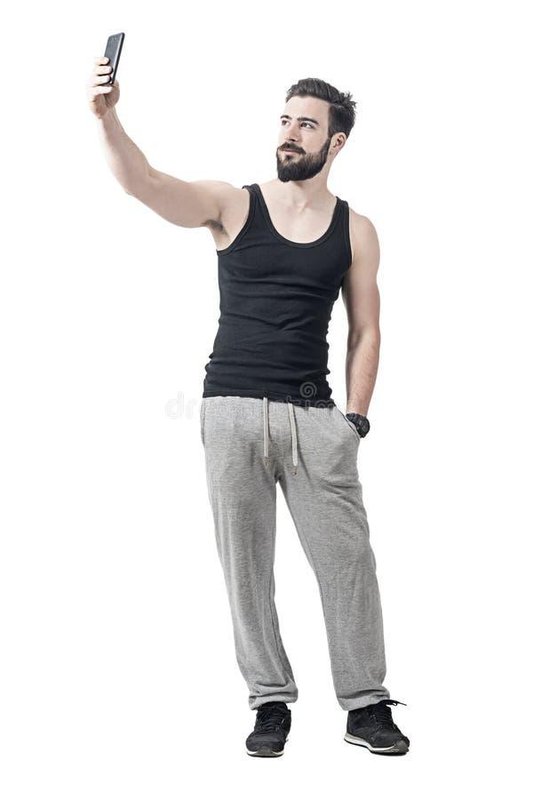 英俊的采取与手机的适合有胡子的年轻人selfie 免版税图库摄影