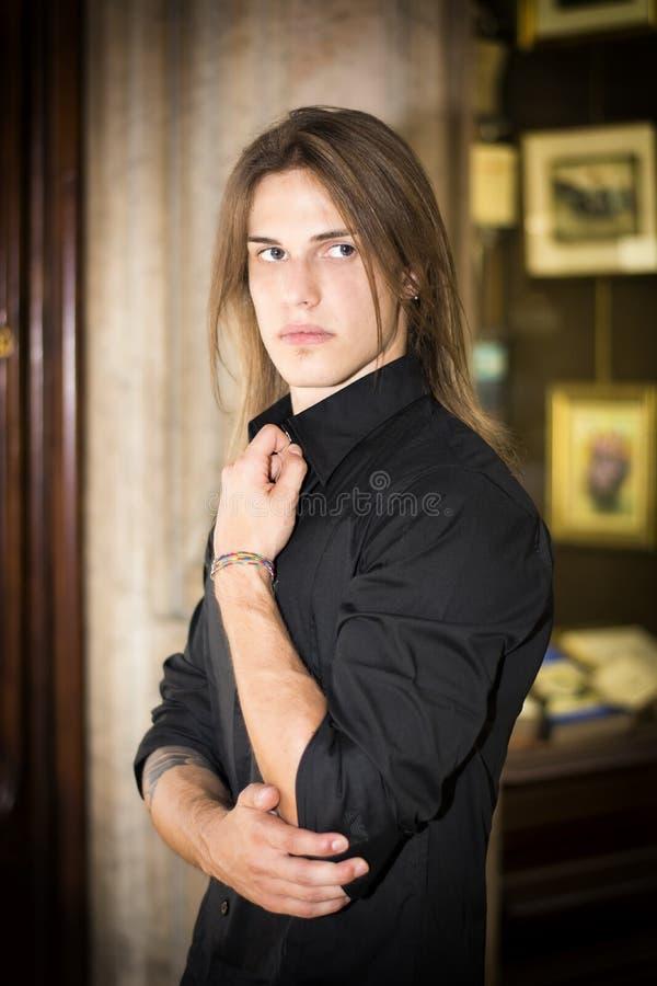 英俊的长的在商店窗口前面的头发年轻人 库存照片