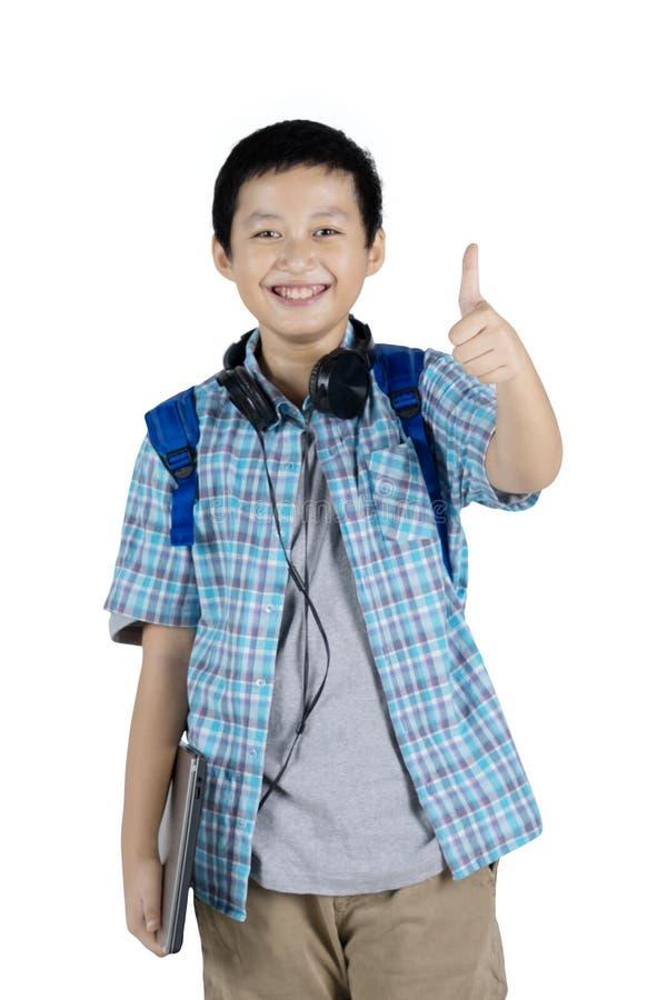 英俊的青少年的学生显示他的在演播室的拇指 免版税图库摄影