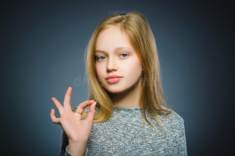 英俊的青少年的展示Ok孤立特写镜头画象在灰色背景的 免版税库存照片