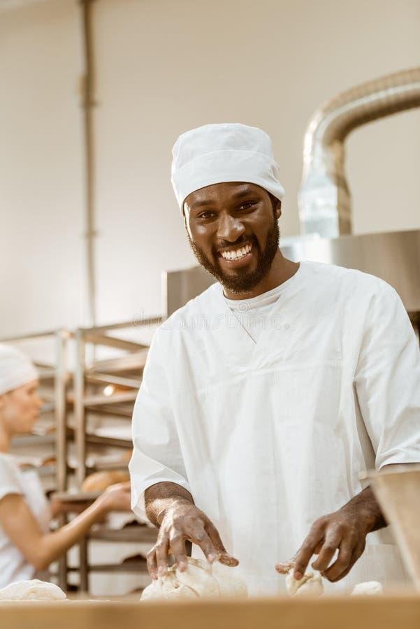 英俊的非裔美国人的面包师揉的面团 免版税库存照片