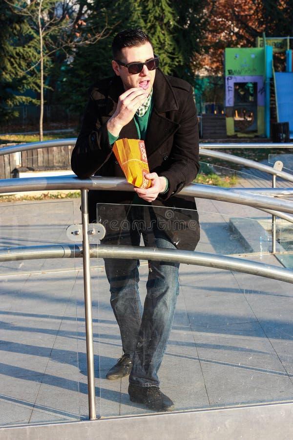 英俊的食人的玉米花外面在公园 库存照片