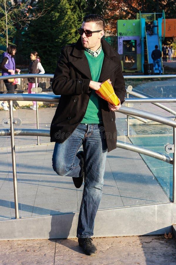 英俊的食人的玉米花外面在公园 免版税图库摄影