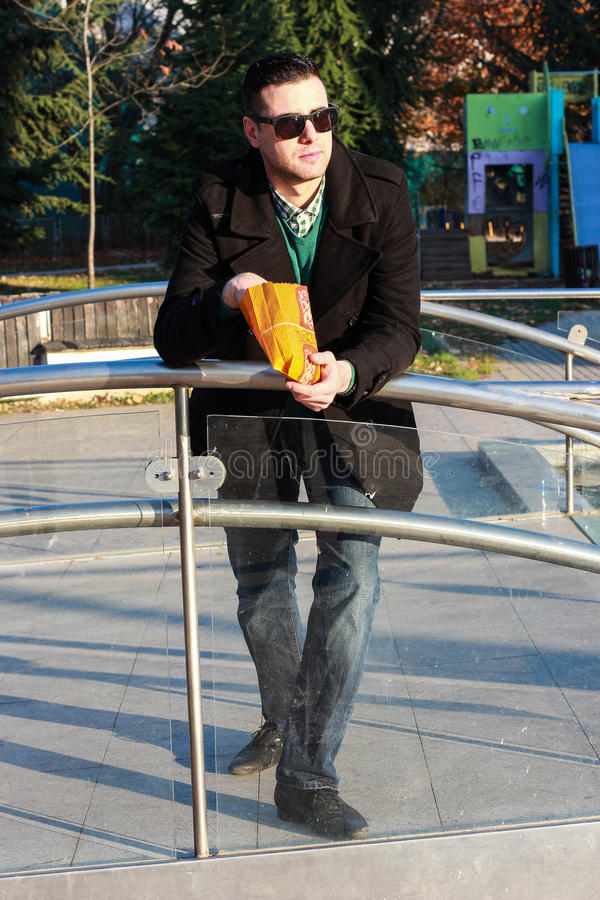 英俊的食人的玉米花外面在公园 免版税库存图片