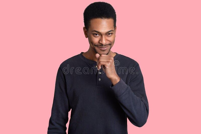 英俊的黑人年轻人室内射击握下巴,看与喜悦的狡猾表情,穿偶然毛线衣,听 库存照片