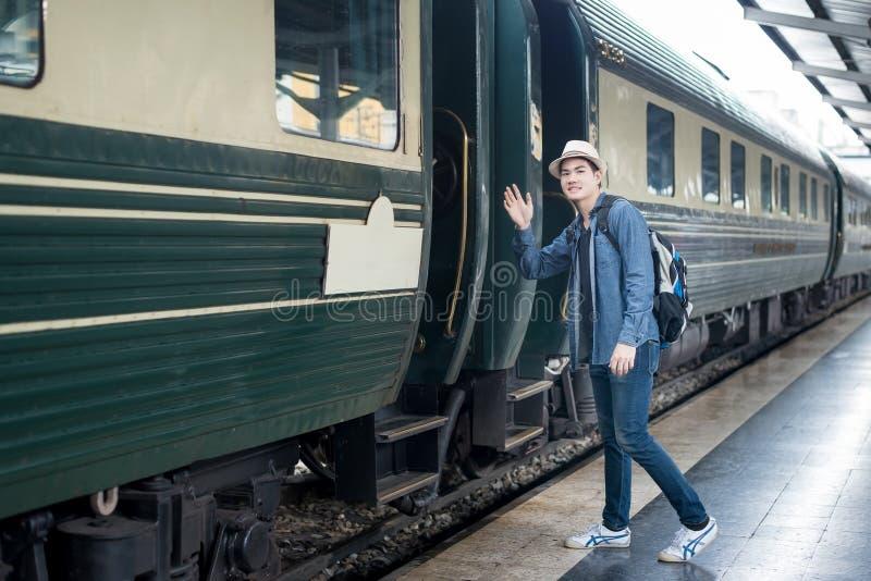 英俊的年轻亚裔人向女朋友说再见在火车stat 免版税库存照片