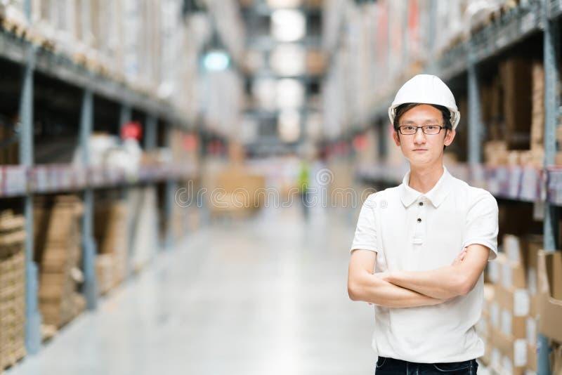 英俊的年轻亚洲工程师或技术员或者工作者、仓库或工厂迷离背景、产业或者后勤指导方针 免版税库存图片