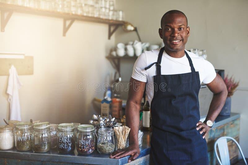 英俊的黑人企业家坚持咖啡馆柜台 免版税图库摄影