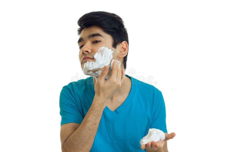 英俊的年轻人喜欢刮的泡沫,并且人在白色背景被隔绝 库存照片