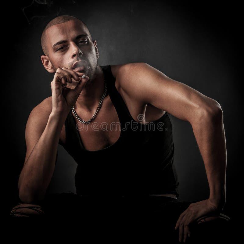 英俊的年轻人在黑暗-摄影中抽香烟  免版税库存图片