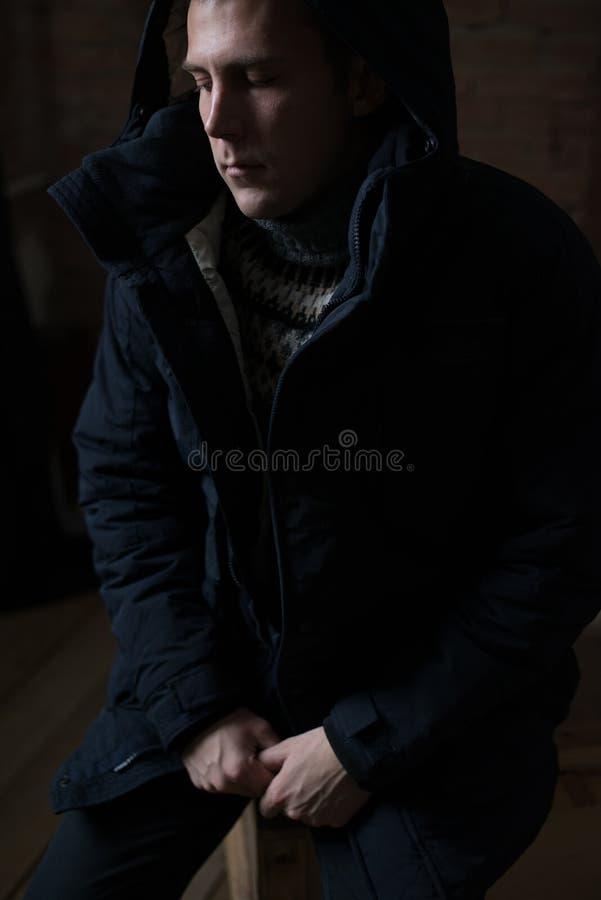 英俊的年轻人在黑暗-摄影中抽香烟 库存图片