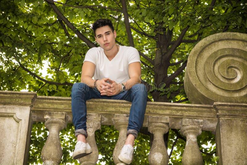英俊的年轻人坐阳台或桥梁 免版税库存照片