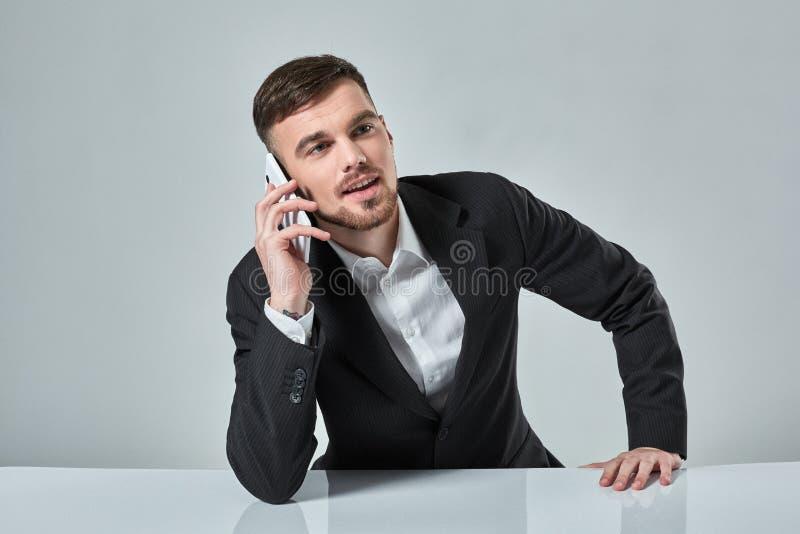 英俊的年轻人谈话在手机,当坐在他的工作地点在办公室时 免版税库存图片
