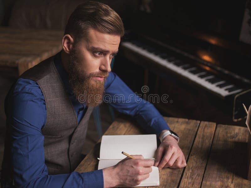 英俊的年轻作家写着一本书 图库摄影