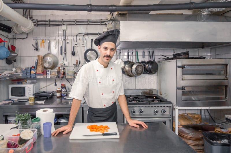 英俊的年轻厨师,商业厨房 免版税库存照片