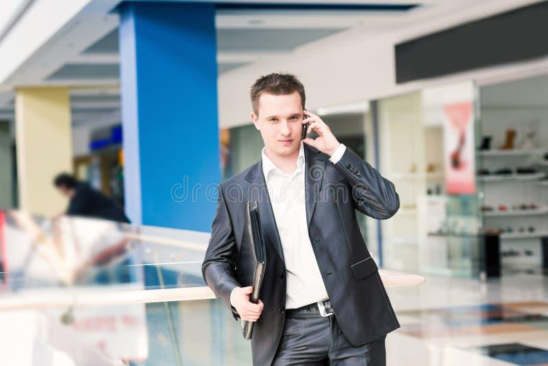 英俊的年轻商人谈话在他的机动性 免版税库存图片