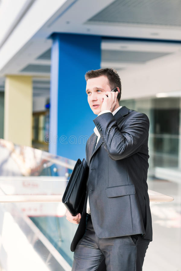 英俊的年轻商人谈话在他的机动性 库存照片