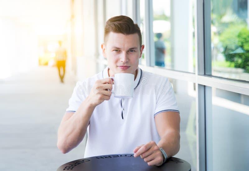 英俊的年轻在咖啡馆的人坐的和饮用的咖啡 库存照片