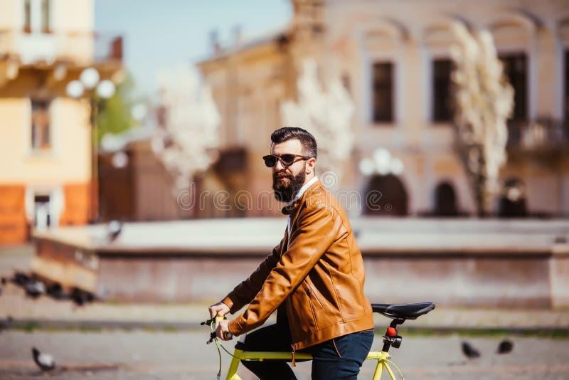 英俊的年轻有胡子的人侧视图看起来的太阳镜的去,当乘坐在他的自行车户外时 库存照片