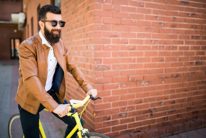 英俊的年轻有胡子的人,当站立在他的自行车附近对砖墙时 图库摄影