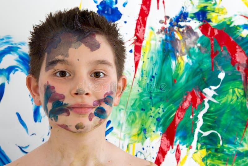 英俊的年轻男孩涂与五颜六色的油漆 图库摄影