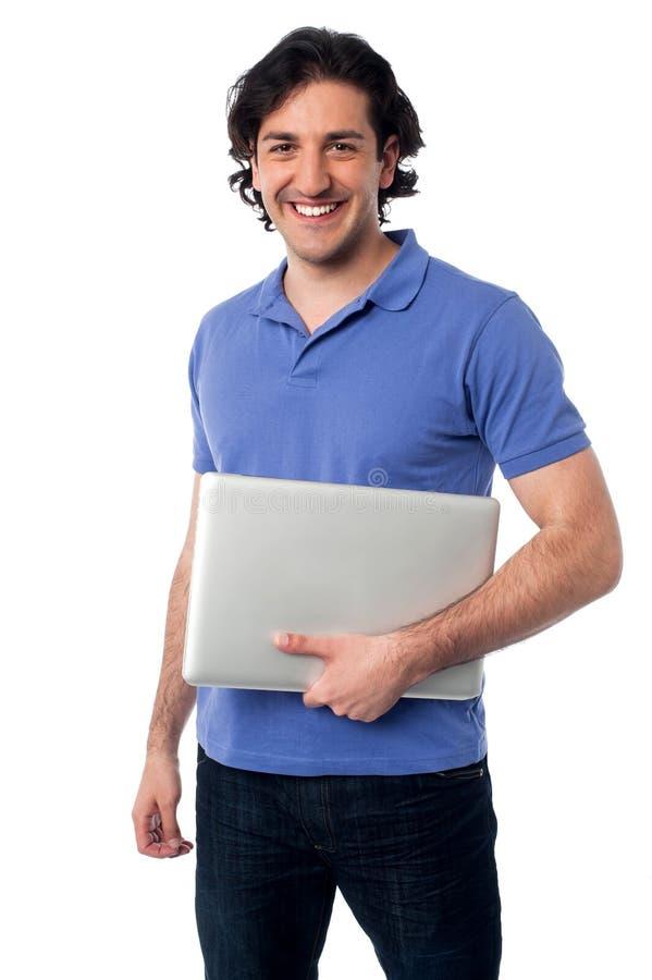 英俊的年轻男性举行的膝上型计算机 库存照片