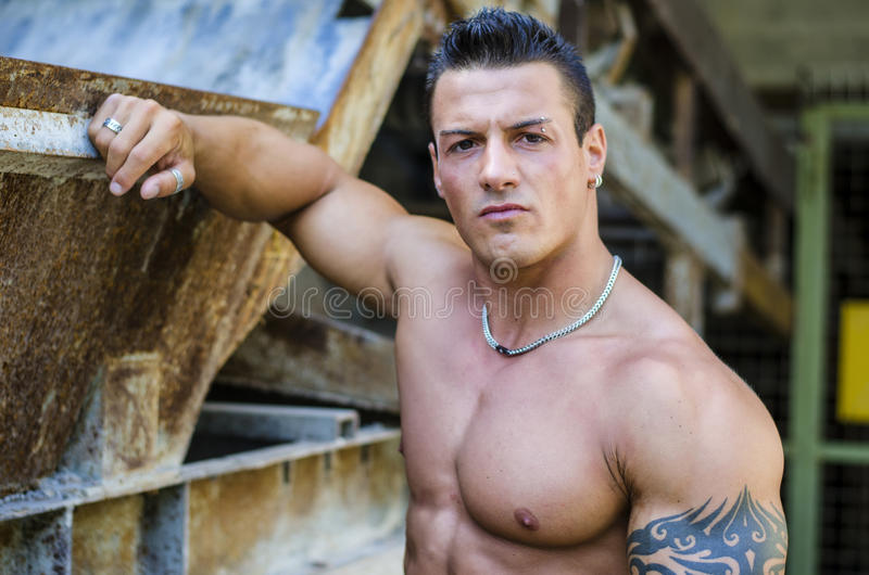 英俊的年轻肌肉人用在生锈的金属结构的手 免版税图库摄影