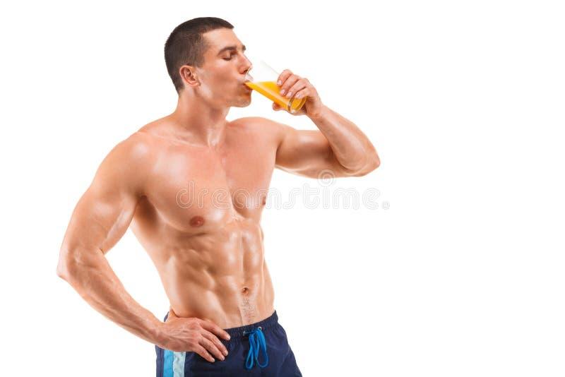 英俊的年轻肌肉在白色背景隔绝的人饮用的汁液 免版税库存照片