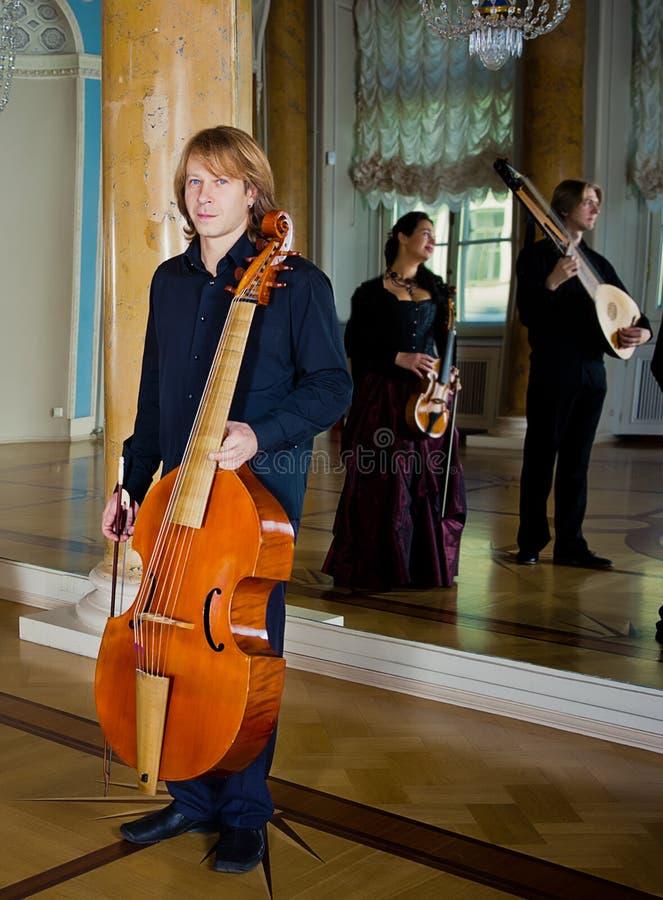 英俊的年轻音乐家戏剧古大提琴在宫殿 免版税库存图片