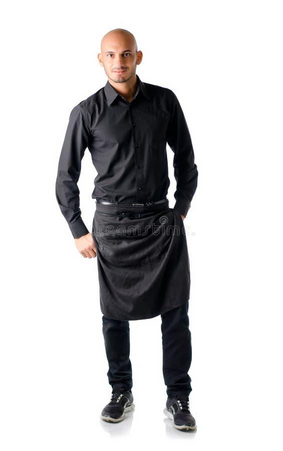 英俊的年轻餐馆或酒吧侍者,站立在白色 免版税库存图片