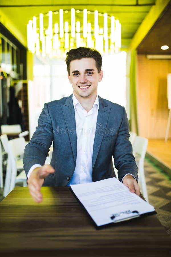 英俊的buisnessman用开放手准备好握手在合同前的标志在他的工作场所在办公室 免版税库存图片