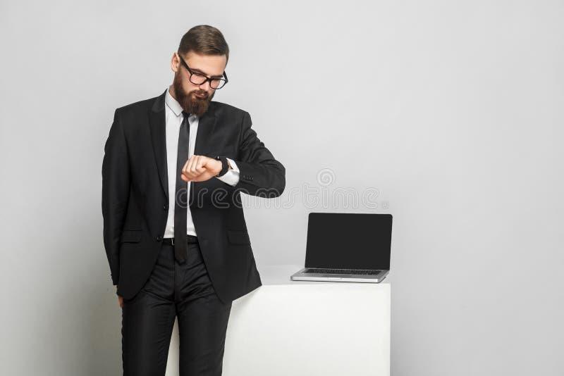 英俊的thoughful有胡子的年轻商人画象在corporated格式穿戴的在黑衣服是站立和检查时间  库存图片