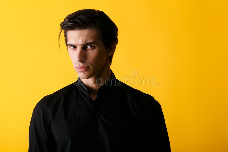 英俊黑衬衣的一严肃的年轻人,看与态度照相机,隔绝在黄色背景 库存照片
