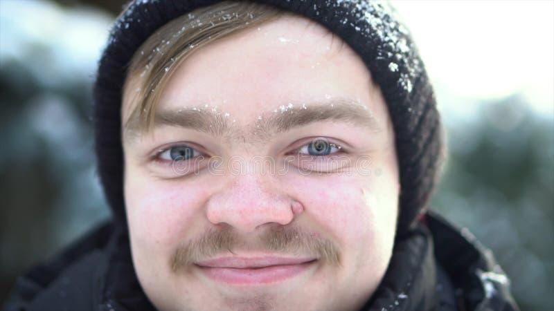 英俊,快乐的人画象有在有雪的冬季衣服穿戴的髭的在他的面孔 为白肤金发关闭  免版税库存图片