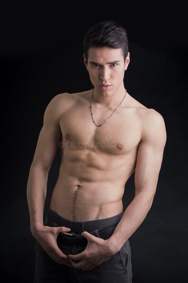 英俊,穿仅裤子的适合赤裸上身的年轻人 免版税库存照片