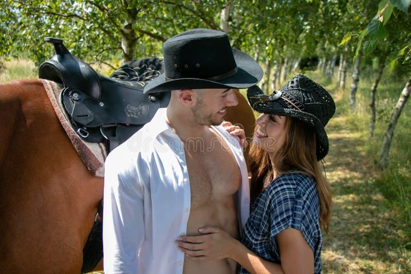 英俊,美好的牛仔和女牛仔加上马和马鞍在举行和亲吻在大农场的大农场 免版税库存图片
