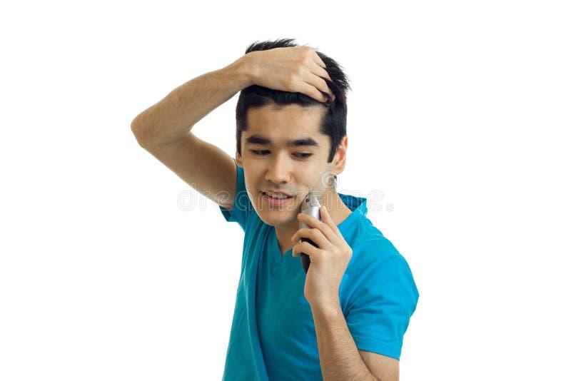 英俊年轻人微笑在白色背景保留手头发神色并且刮他的胡子被隔绝 图库摄影