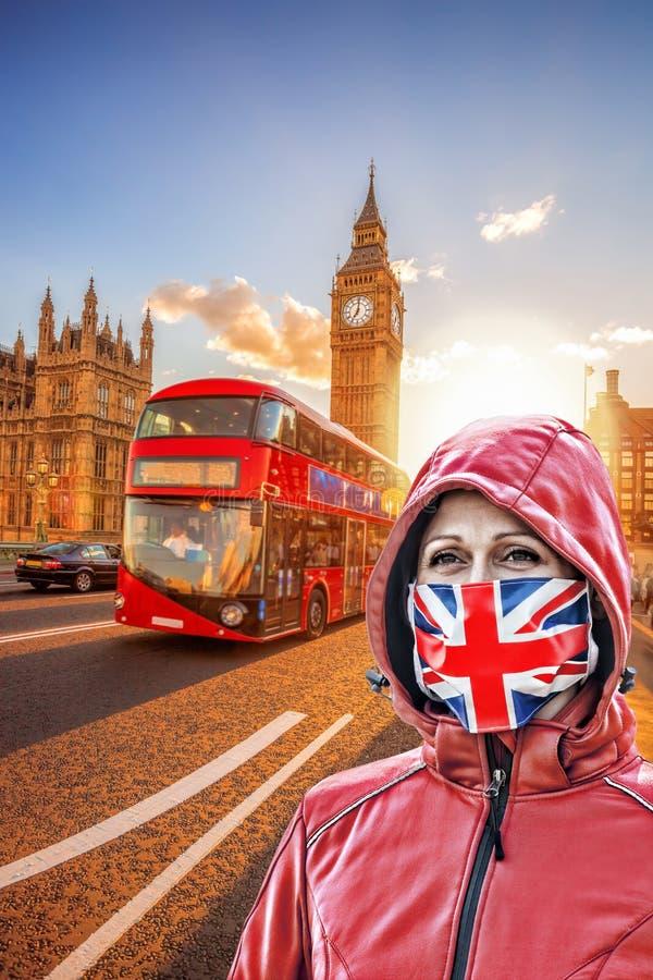 英国伦敦大本钟前戴英国国旗防冠状病毒防护面罩的女子 免版税库存照片