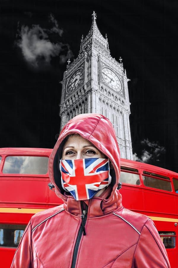英国伦敦大本钟前戴英国国旗防冠状病毒防护面罩的女子 免版税图库摄影
