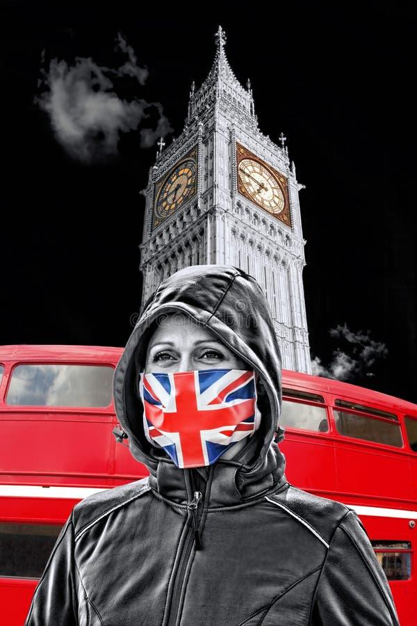 英国伦敦大本钟前戴英国国旗防冠状病毒防护面罩的女子 库存图片