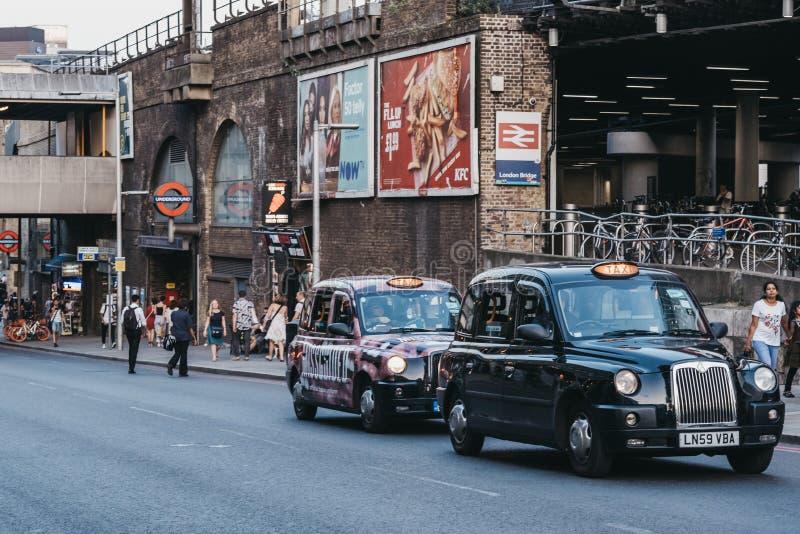 英国伦敦大桥站外黑色出租车 免版税库存照片