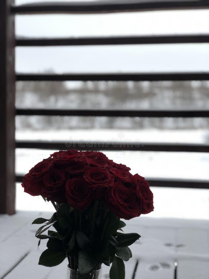 英国兰开斯特家族族徽花束在一个花瓶的在一个积雪的木棕色阳台在冬天森林的背景的一栋乡间别墅里 库存图片