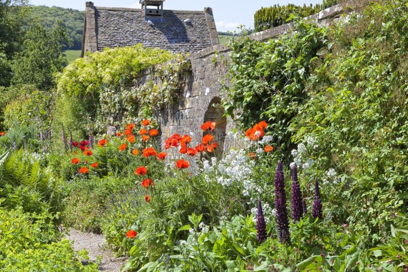 英国有石墙的村庄夏天花园 免版税库存图片