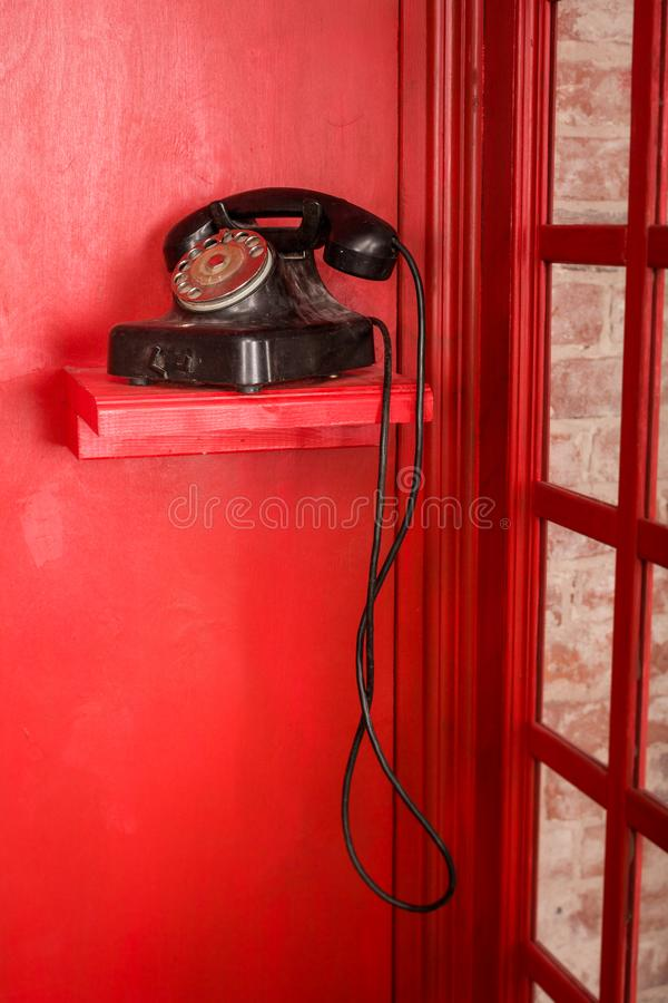 英国样式的红色电话亭 有站立在它的黑减速火箭的电话的英国电话箱子 库存照片