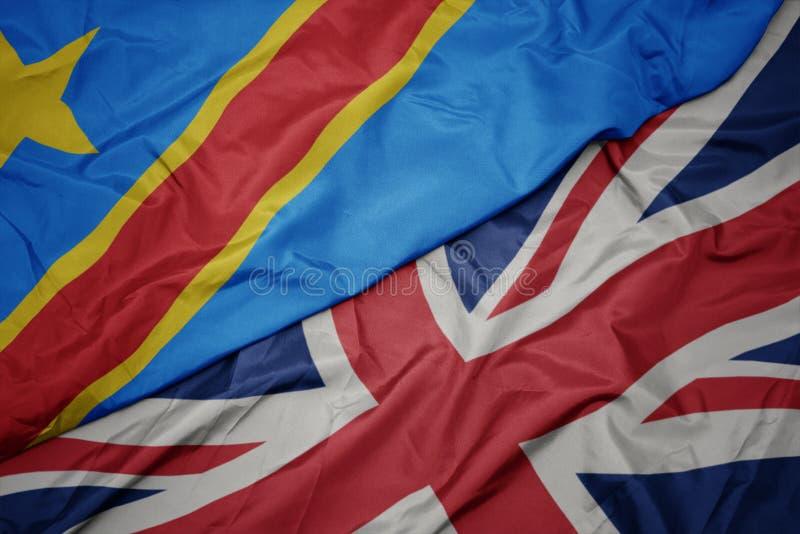 英国的挥动的五颜六色的旗子和刚果民主共和国的国旗 库存图片