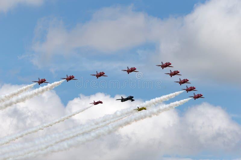英国皇家空军红色箭头合作在形成与叫卖小贩猎人和一个对的飞行Folland蚋 免版税库存图片
