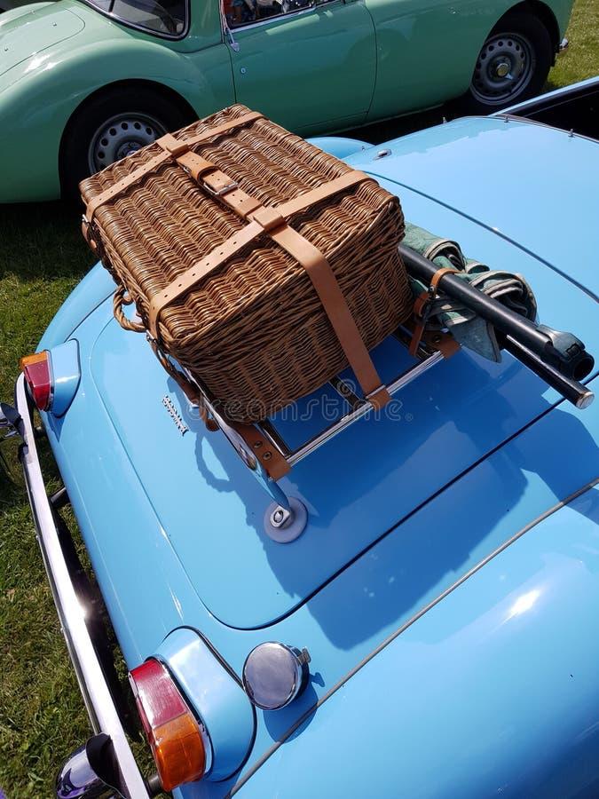 英国经典跑车后面的柳条野餐篮 图库摄影