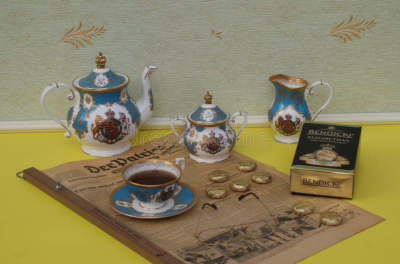 英国茶具、Bendick的伊丽莎白女王的巧克力薄菏包裹和在一个老德国报纸范德默韦爱国者的放大镜 免版税库存照片