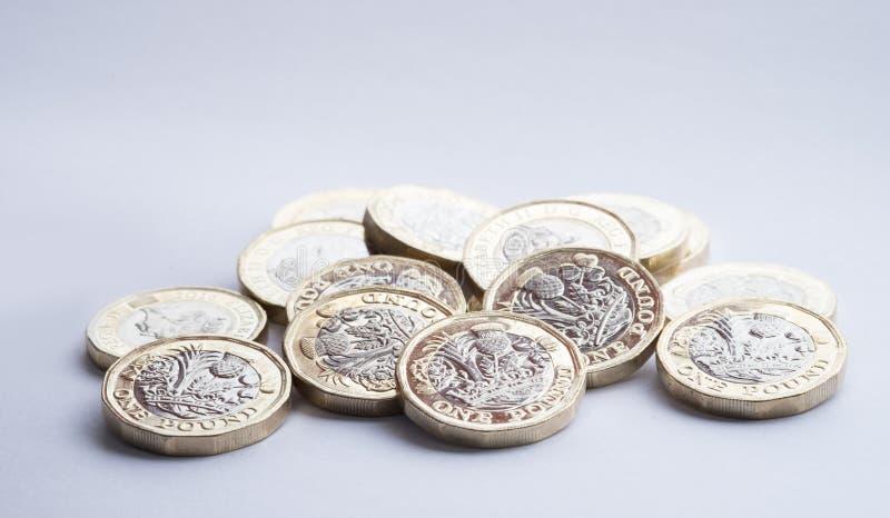 英国金钱,在小堆的新的1英镑硬币 免版税库存照片