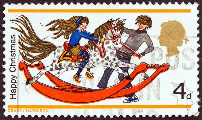 英国-大约1968年:在英国打印的邮票显示男孩和女孩有摇马的,大约1968年 免版税图库摄影